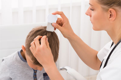 Child with head lice being treated by a nurse