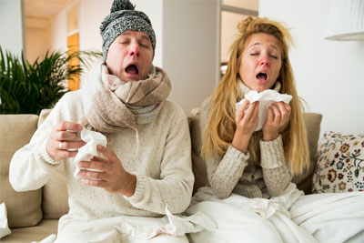 Husband and wife with common cold sneezing
