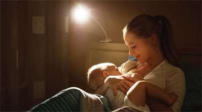 Mom Breastfeeding Baby at Night Before Bed