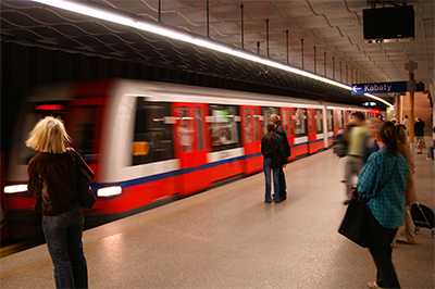 Passengers on subway platform as train passes by