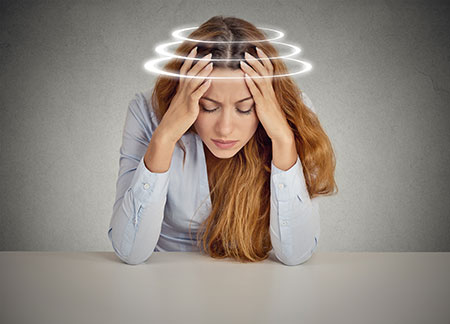 Woman suffering from vertigo dizziness nausea